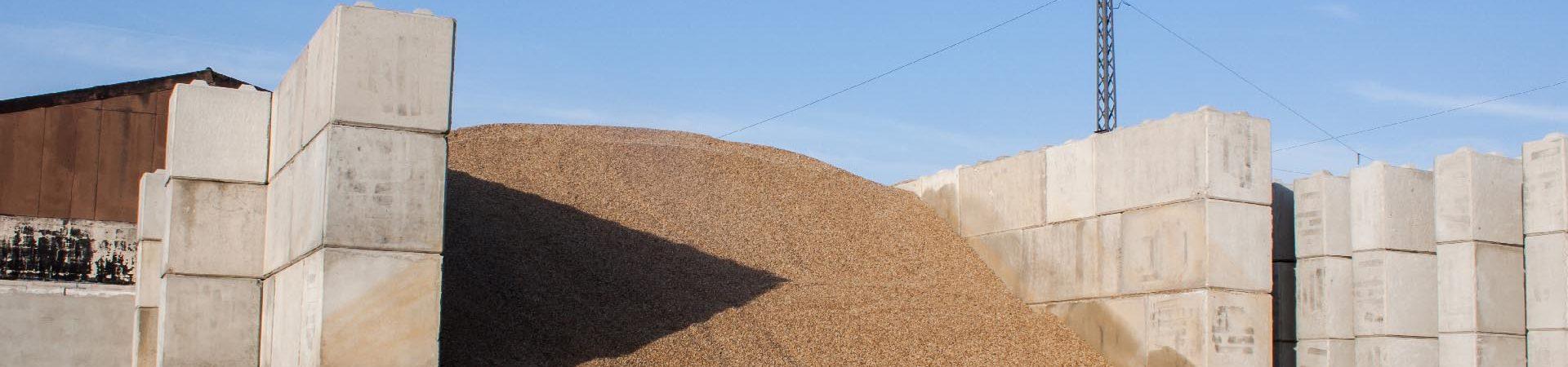 Bagger schaufelt Sand-Geröll-Gemisch bei blauem Himmel